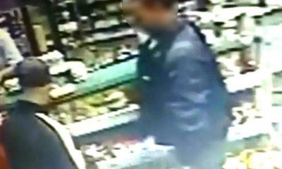 Uma das vítimas,mantida sob a mira do revólver, entrega o celular para o assaltante — Foto: Câmeras de segurança/Reprodução