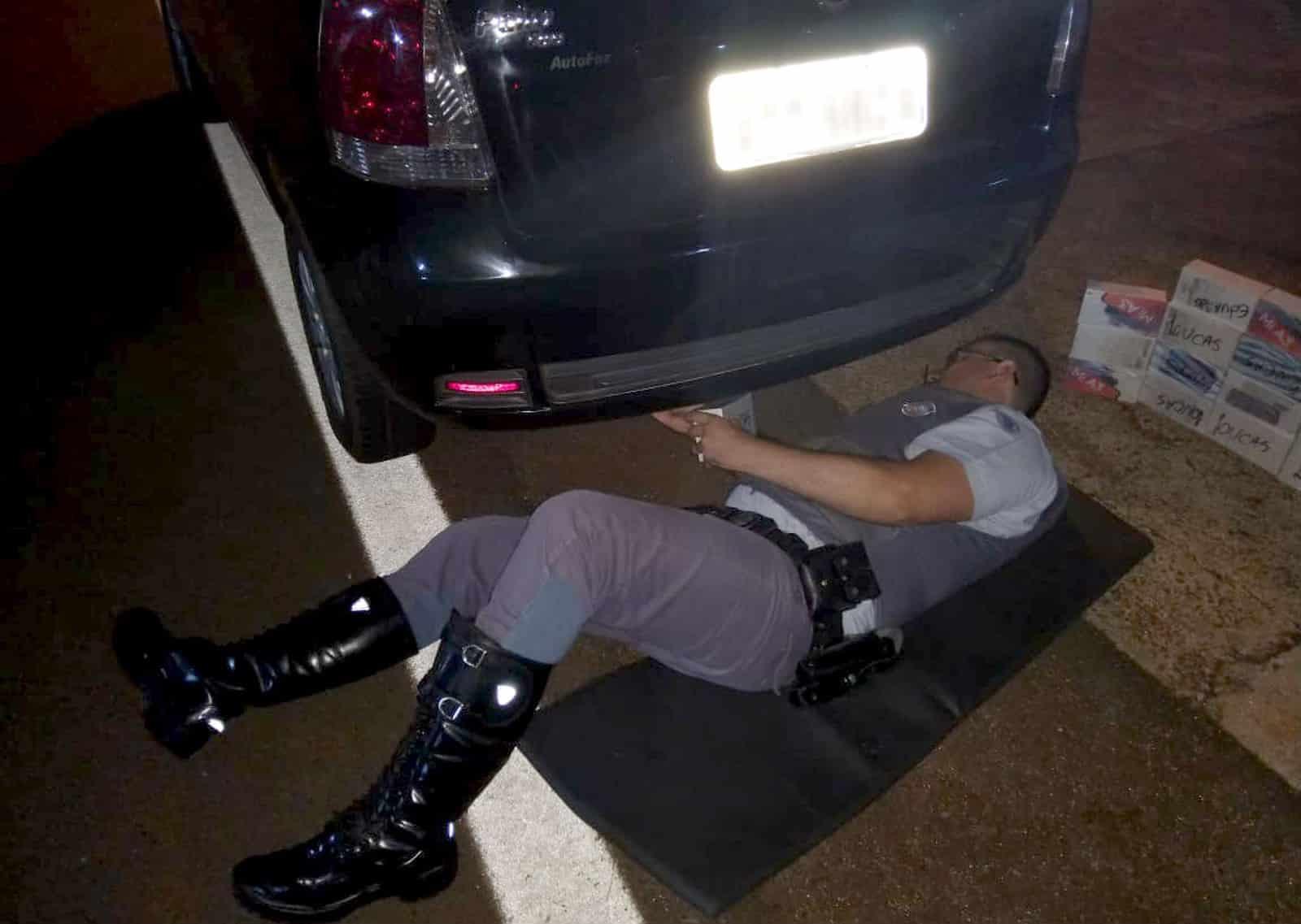 Policial durante revista ao veículo que tinha produtos sem nota fiscal escondidos dentro do para-choque — Foto: Polícia Rodoviária/Divulgação'