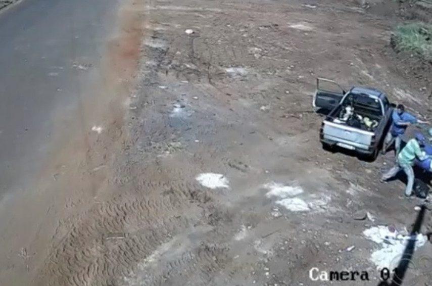 Imagens mostram carro parando no local e dois homens jogando material que estavam na caçamba do veículo — Foto: Câmera de segurança/Reprodução